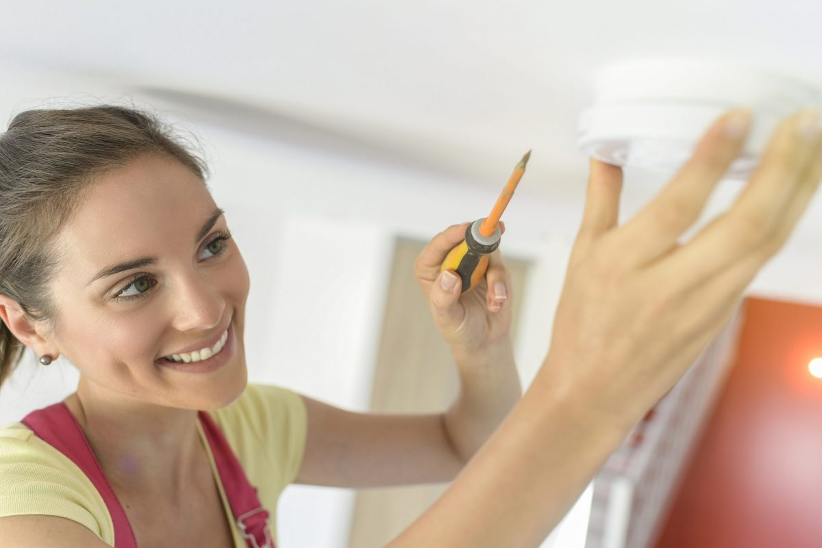 Young woman is fitting a fire alarm in the ceiling
